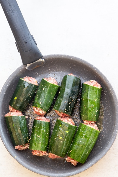 the zucchini stuffed and read for cooking in a black pan