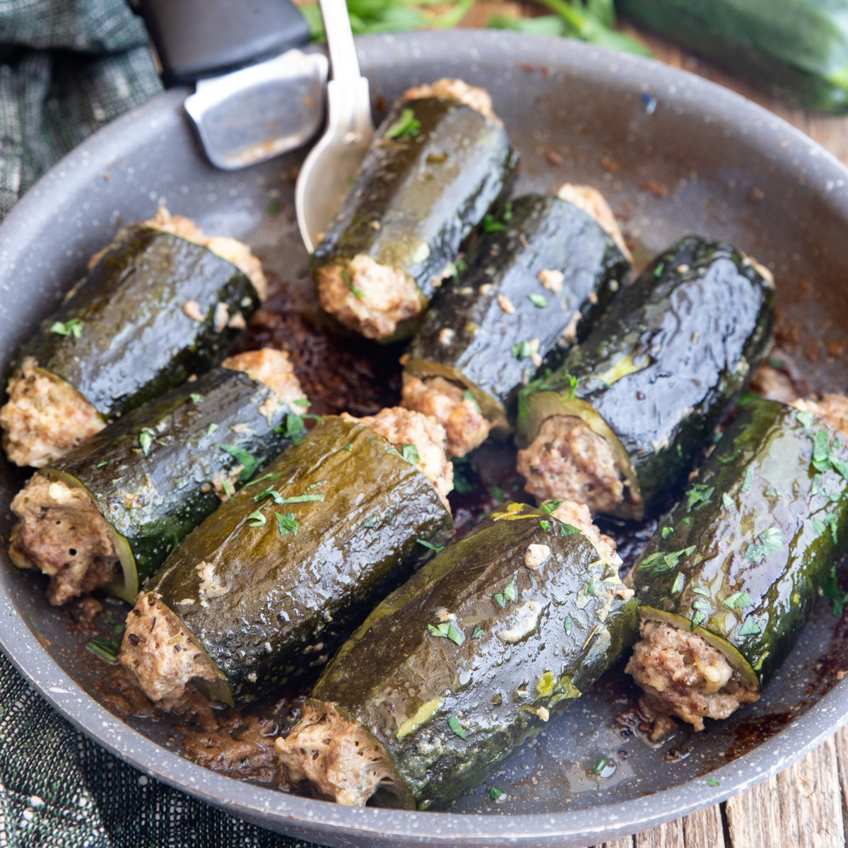 stuffed zucchini with a silver spoon in a black pan