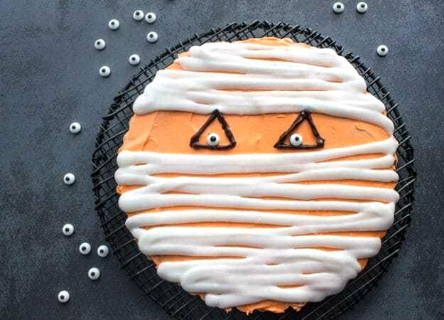 chocolate chip cookie cake mummy face on a black wire rack