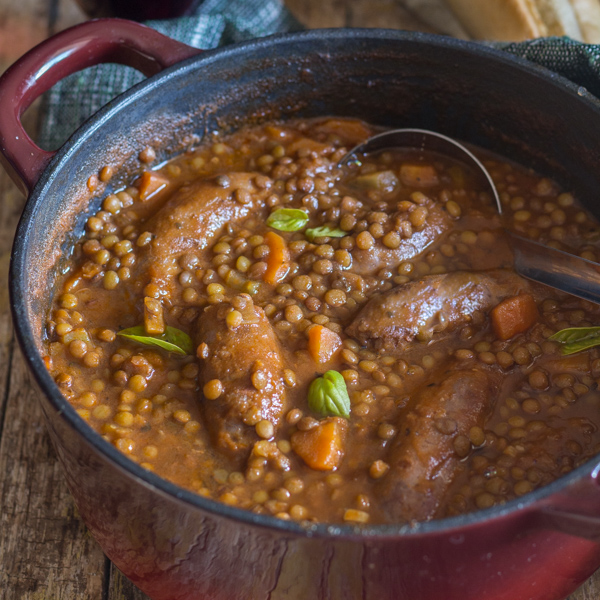 lentils and sausage stew in a red pot