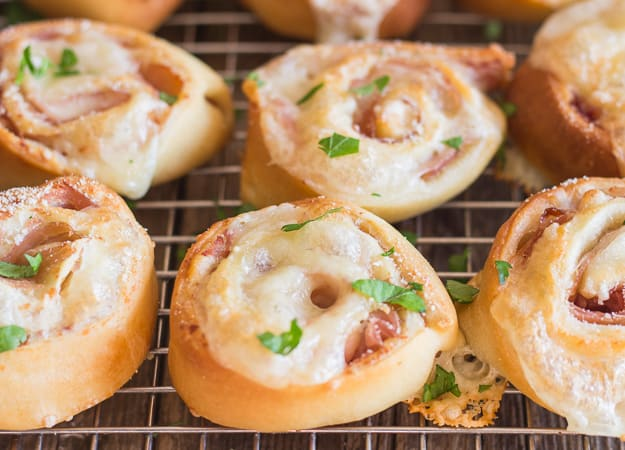 ham and cheese pizza roll ups on a wire rack