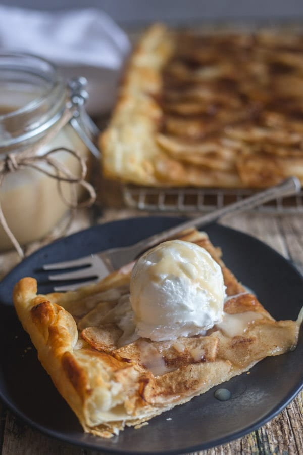 apple tart slice on a black plate and on a wire rack