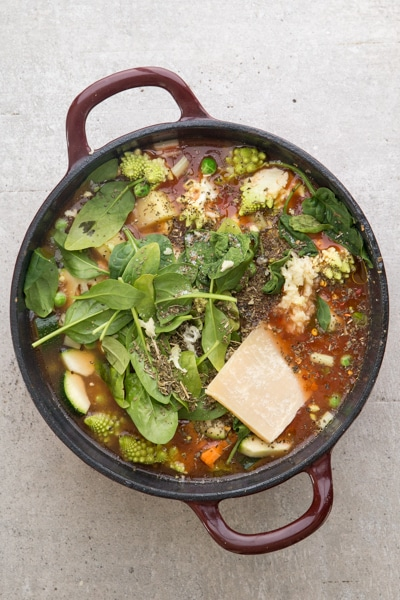 adding all the ingredients for the soup in a red pot
