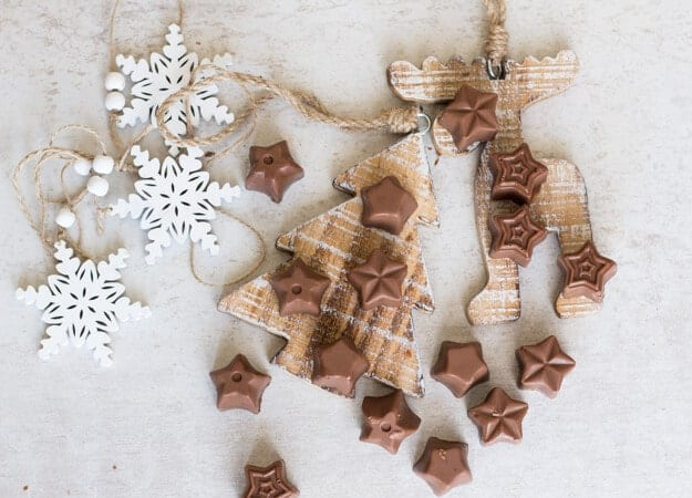 chocolates on a christmas tree board and on a white board with wooden white snowflakes