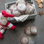 cookies in a grey wooden box with santa leaning against it with 3 cookies on the board