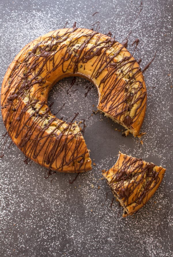 chocolate chip bundt cake drizzled with chocolate on a black board with a piece cut out