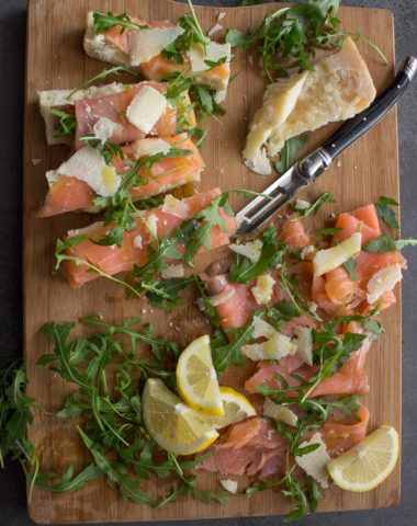 smoked salmon slices, parmesan cheese chunks, rucola leaves, lemon slices and a knife on a wooden board