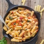 basil tomato sauce with pasta in an iron skillet