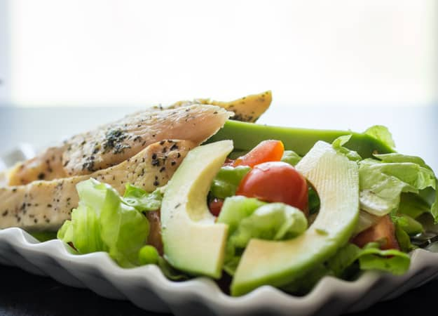 grilled chicken with salad on a white plate