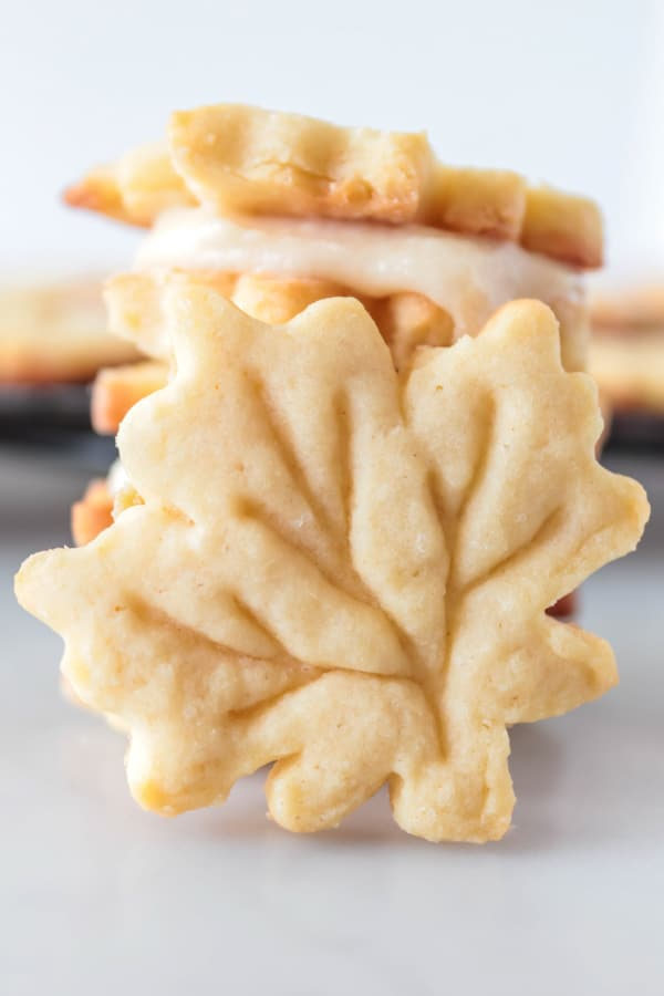 3 maple leaf cookies stacked with one leaning against them