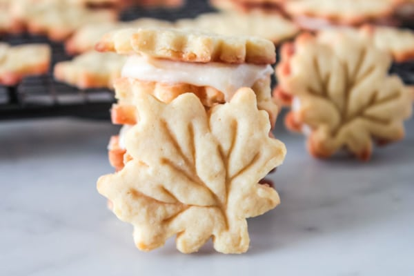 maple leaf cookies stacked with one leaning against them and some on a wire rack with one leaning in the background