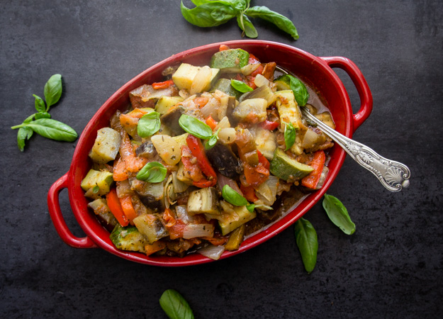 top view of cooked ratatouille in a red casserole dish on a black board with basil leaves