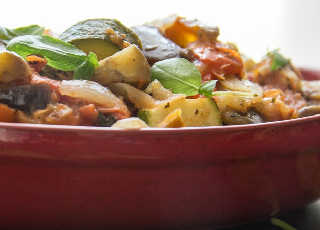 a close up of cooked Ratatouille in a red casserole dish