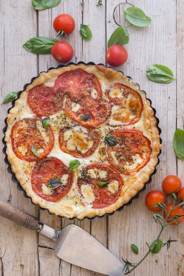 tomato pie on a white board with cherry tomatoes around it