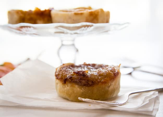 3 old fashioned butter tarts on a cake stand and one on wax paper with a fork