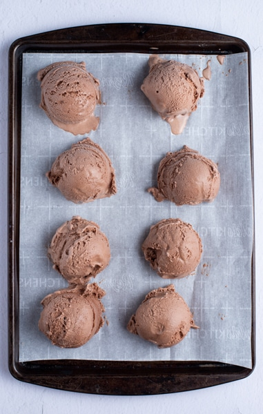 Ice cream scoops on a parchment paper cookie sheet.
