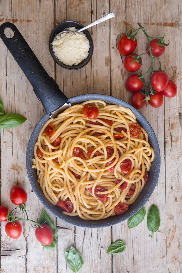roasted parmesan tomatoes and bucatini pasta in a pan