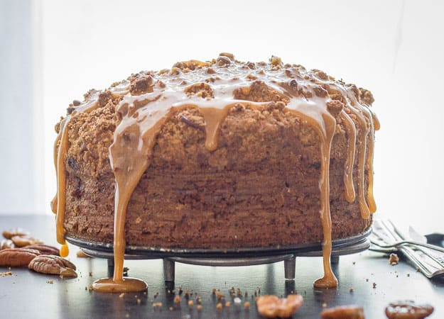 cake with caramel drizzle on a black cake stand
