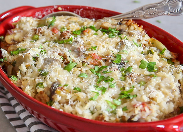 rice casserole in a red baking dish with a serving spoon