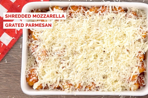 Gnocchi in baking pan with cheese on top before baking.