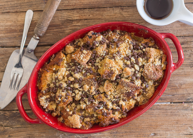 baked panettone french toast casserole in a red baking dish with a spatula and a fork on a wooden board