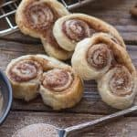 up close of 3 cinnamon sugar puff pastry palmiers on a wooden board