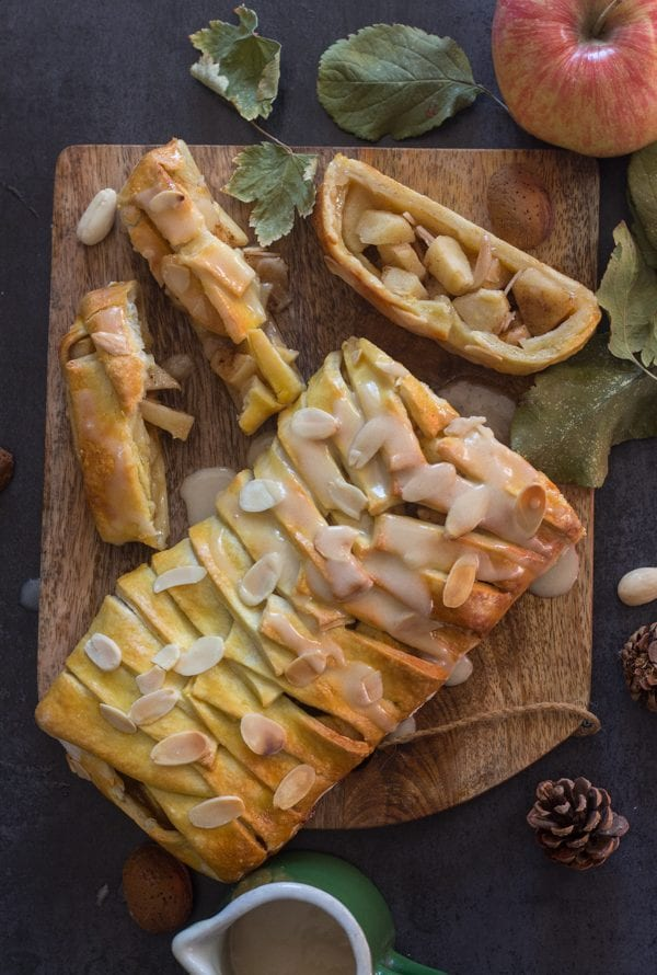 apple cinnamon strudel on a wooden board with 3 pieces cut
