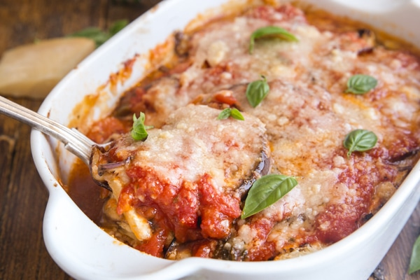 eggplant parmesan baked in a white pan with a spoonful