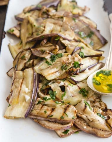 grilled eggplant on a white pan with a silver spoon