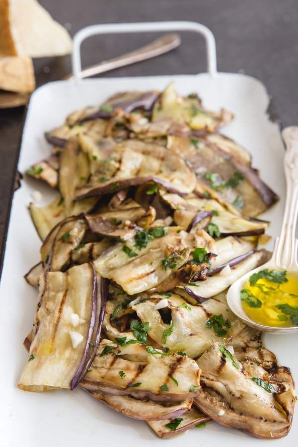grilled eggplant on a white pan with a brass spoon