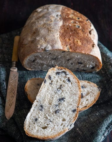 Loaf of olive bread with 2 slices cut and a knife on a blue napkin.