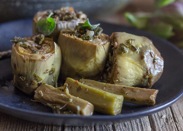cooked roman artichokes on a black plate