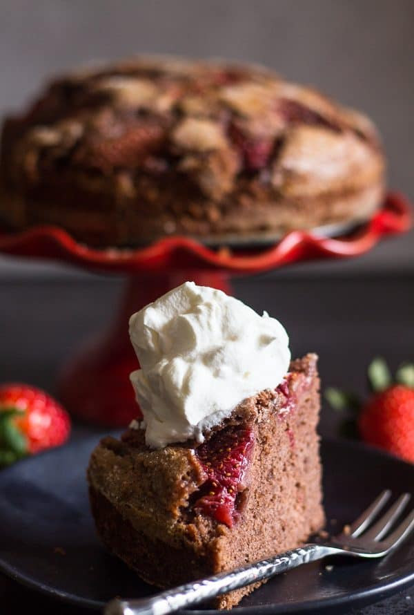strawberry chocolate cake with a slice on a plate with whipped cream