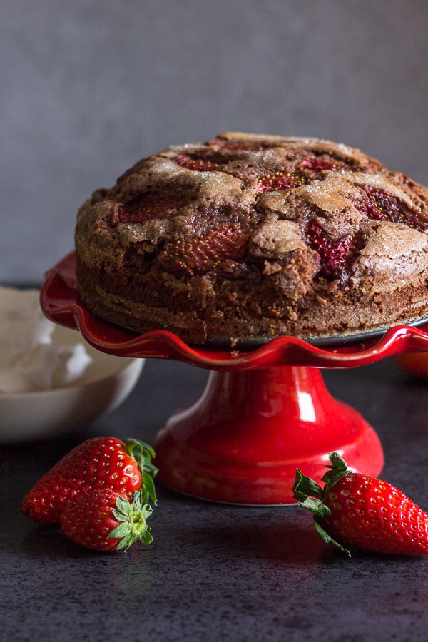 baked chocolate strawberry cake on a red cake stand