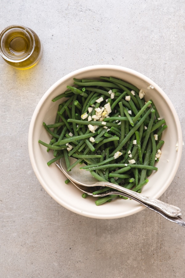cooked green beans with chopped garlic in a white bowl