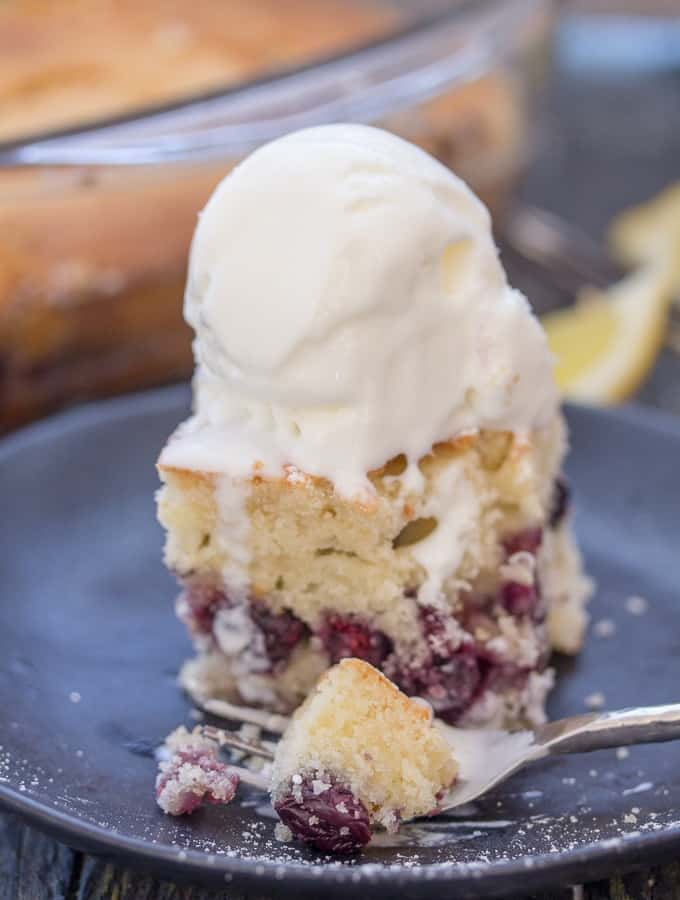 a slice of blueberry cake bars on a black plate with a scoop of ice cream