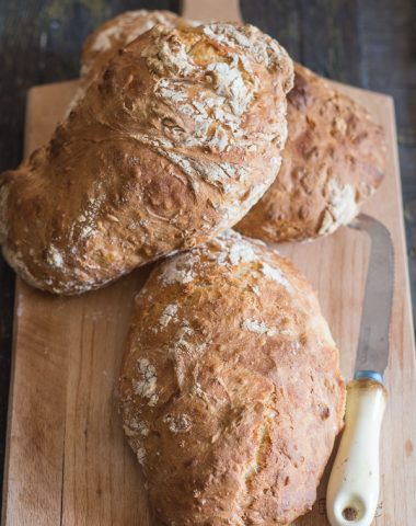 3 no knead bread loaves on a wooden board