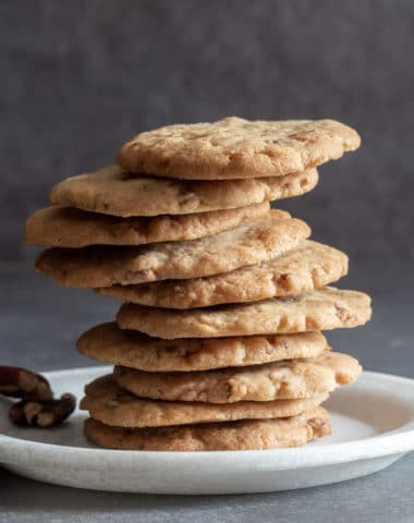 Pecan cookies stacked on a white plate.