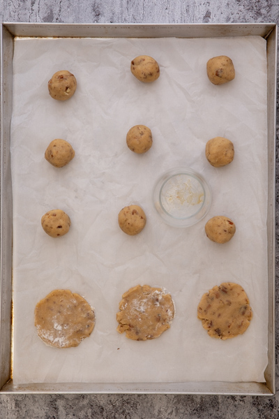 Cookie dough balls on a parchment paper and flattened with a glass.
