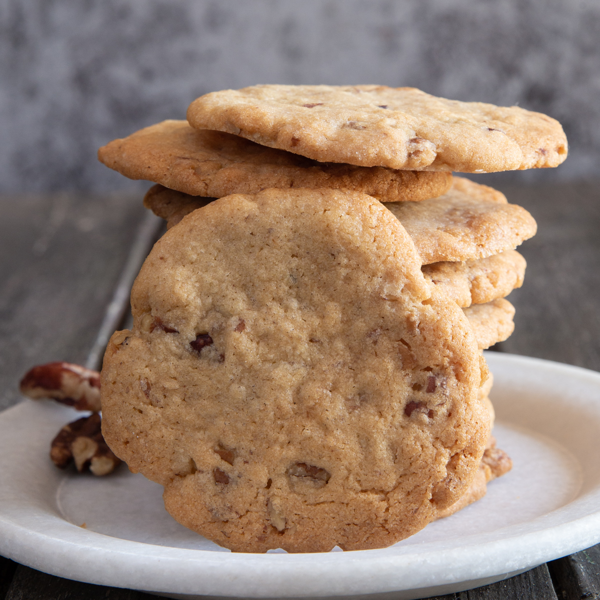 Pecan cookies stacked with one leaning on them.