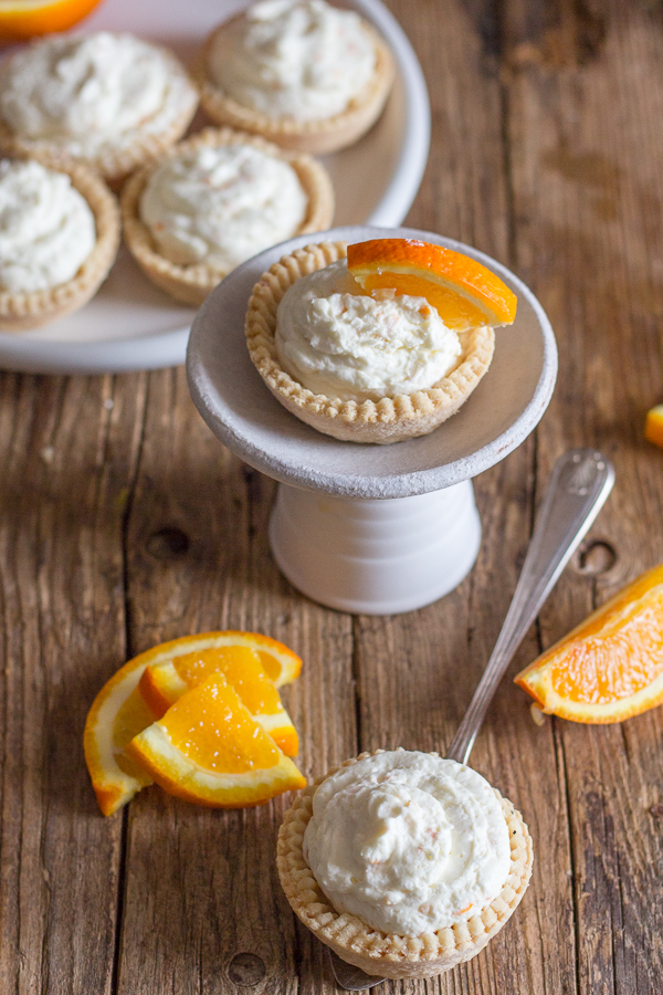 orange cheesecake tarts on a wooden board