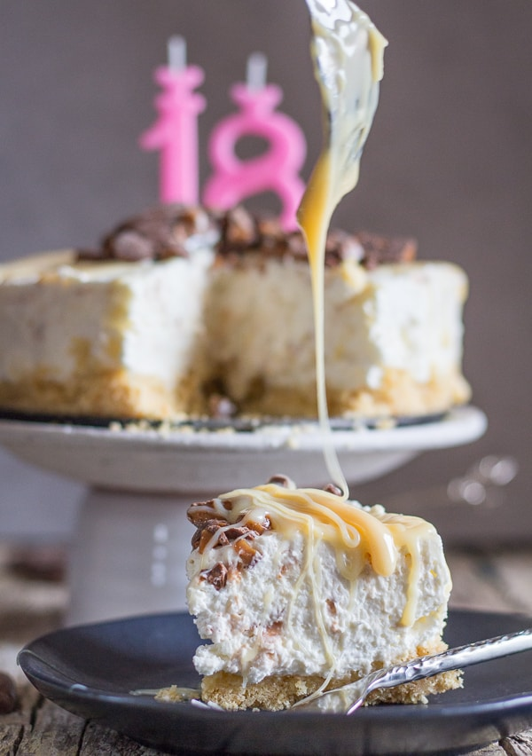 drizzling caramel on a slice of no bake cheesecake