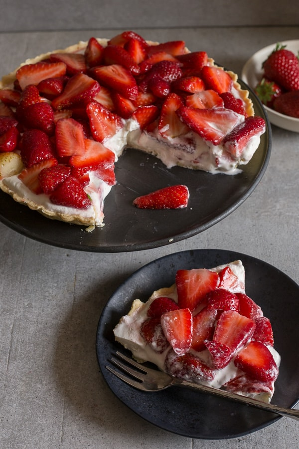 fresh strawberry pie on a black plate and a slice on a plate