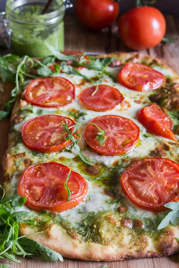 pesto pizza with mozzarella & tomatoes on a board