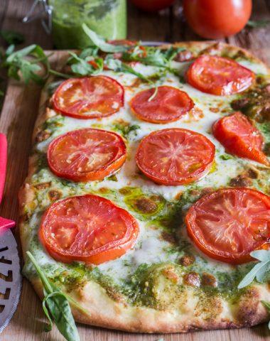 pesto pizza on a wooden board