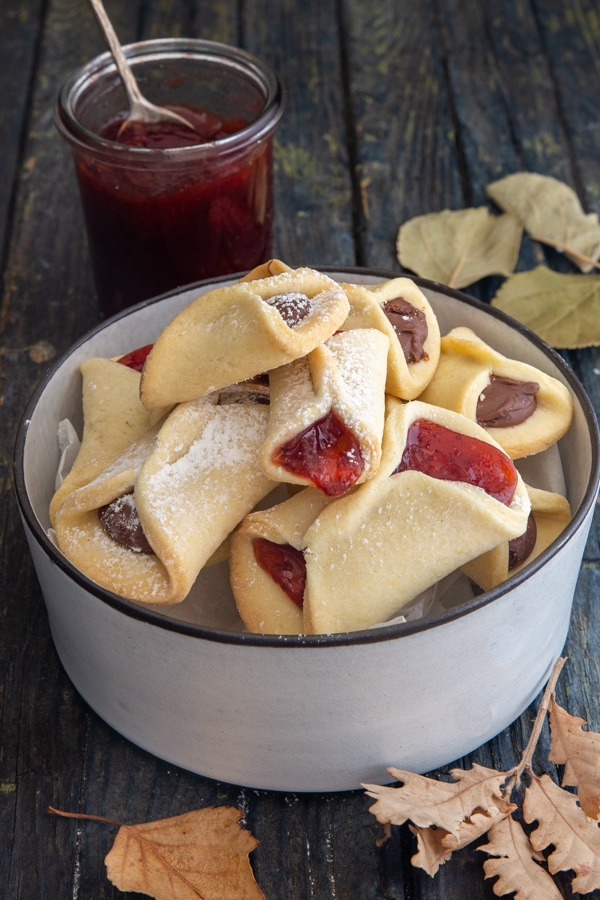 cookies in a white bowl with jam in a jar