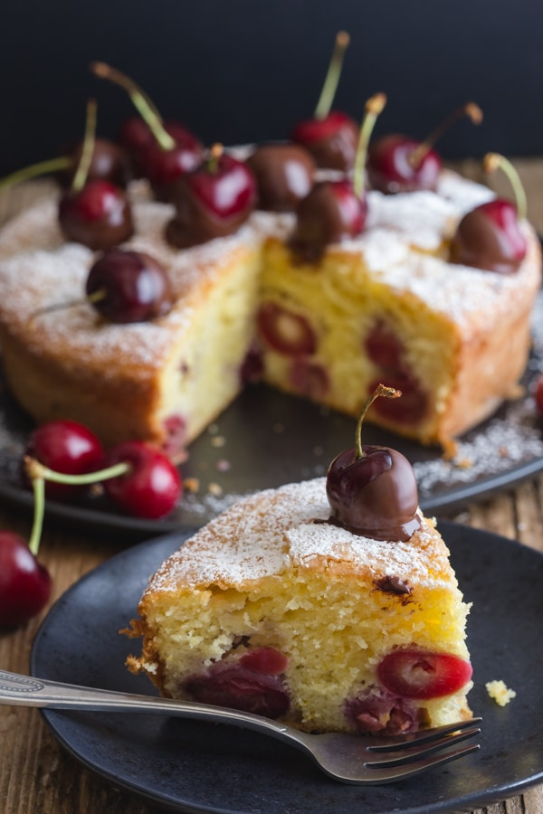 cherry cake with a slice cut on a black plate