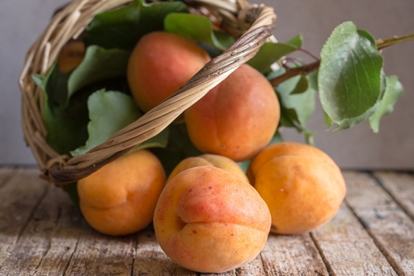 apricots falling out of a basket
