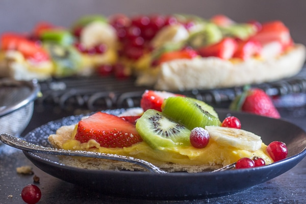 a slice of fruit pizza on a black plate