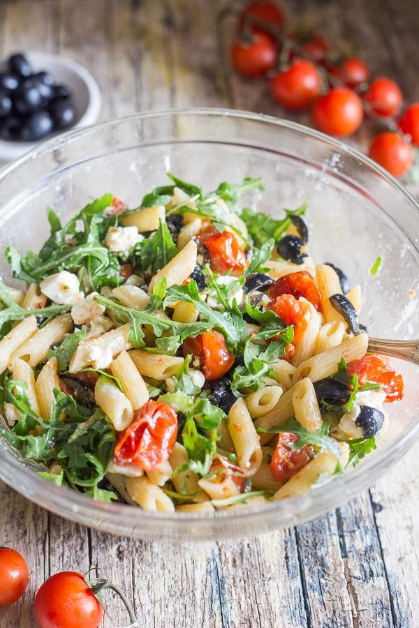 एक कांच के कटोरे में ग्रीक पास्ता सलाद